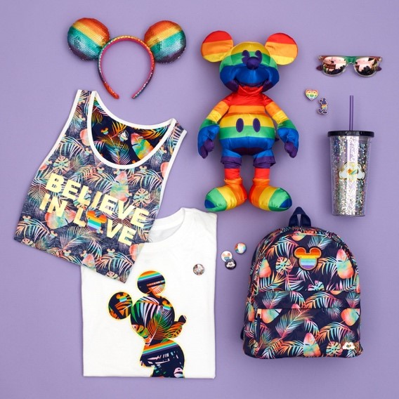 Photograph of the items in Disney Store UK's Rainbow Mickey Collection, including a t-shirt, vest, badges, backpack, plastic drinks cup and rainbow Mickey Mouse soft toy